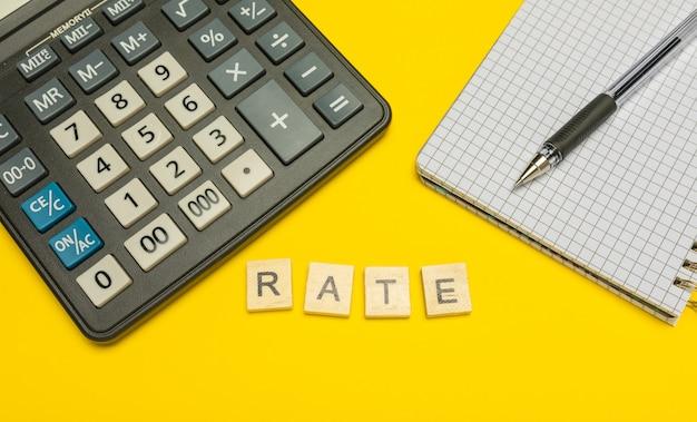 ペンとノートを備えた黄色と現代の電卓に木製の文字で作られた単語率。