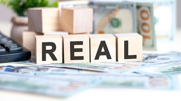 The word real on wood cubes, banknotes and calculator. business, marketing and commerce concept.