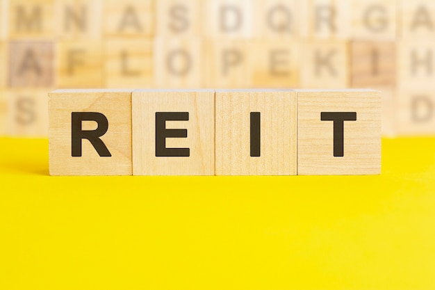 The word reit is written on wooden cubes on a bright yellow surface. in the background are rows of cubes with different letters. business and finance concept