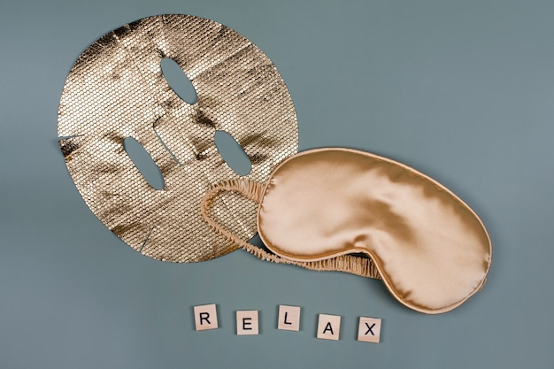 Word relax with golden sleeping eye mask and cosmetic facial sheet mask, flight and travel concept
