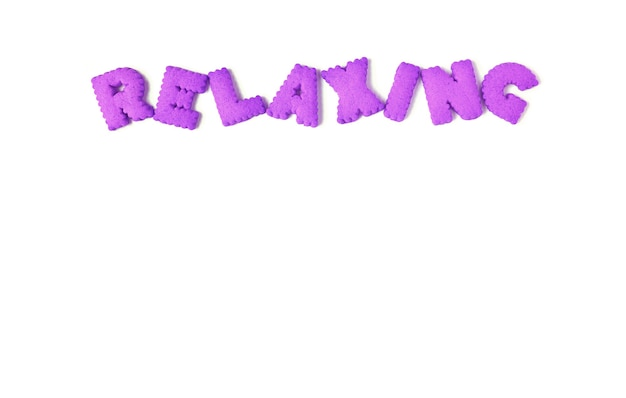 The word relaxing spelled with purple alphabet shaped biscuits on a white background