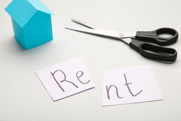 The word 'rent' written on paper and cut in half with a pair of scissors