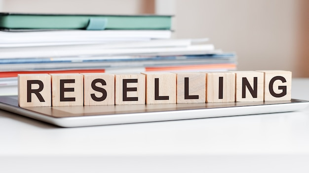 The word reselling is written on wooden cubes standing on a notepad, in the surface a stack of documents