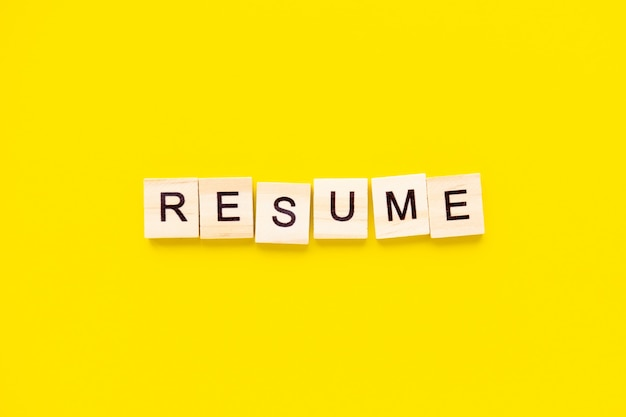Word resume. wooden blocks with lettering on top of yellow table. human resource management and recruitment and hiring concept