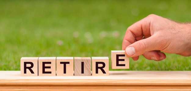 Word retire written with wooden blocks. man hand holding wooden cube block with retire