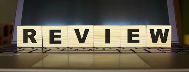 ワードレビュー。ノートパソコンのキーボードで分離された文字と木製の立方体。ビジネス