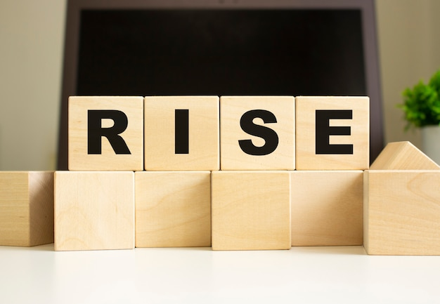The word rise is written on wooden cubes lying on the office table in front of a laptop. business concept.
