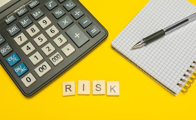 ペンとノートを備えた黄色と現代の電卓の木製の文字で作られた単語のリスク。