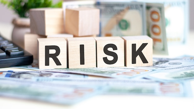 The word risk on wood cubes, banknotes and calculator on the background. can be used for business, marketing and commerce concept