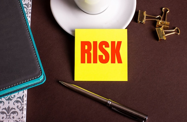 The word risk written on yellow paper on a brown background near a coffee cup and diaries