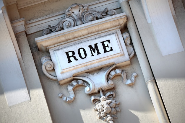 The word rome carved in an old sculpted wall.