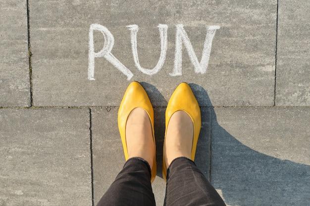 Word run written on gray pavement with woman legs