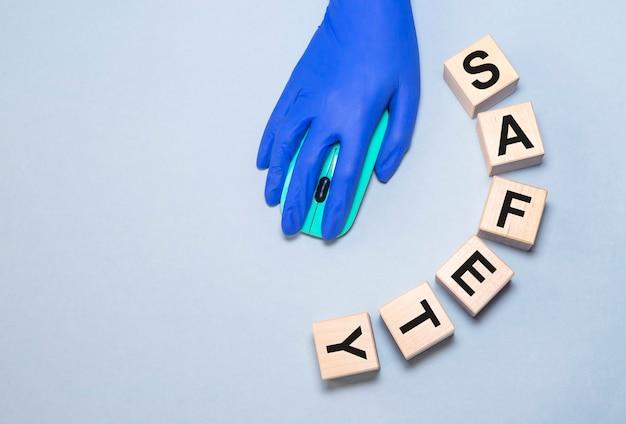 灰色の青色の背景にコンピューターのマウスを使用して、立方体と白いラテックス手袋で手の単語の安全性..。