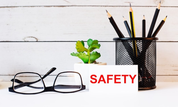 The word safety written on a white business card next to pencils in a stand and glasses. nearby is a potted plant...