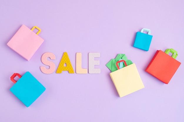 Слово продажа и хозяйственные бумажные пакеты. сезонная распродажа, онлайн-предложения, скидки, продвижение, концепция покупательской зависимости