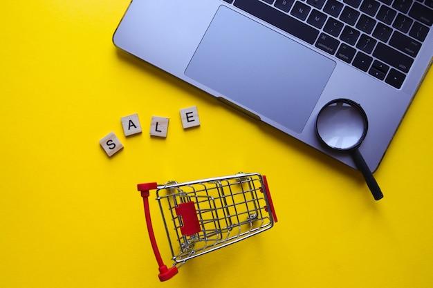 Продажа слова из деревянных букв и продуктовой тележки рядом с ноутбуком