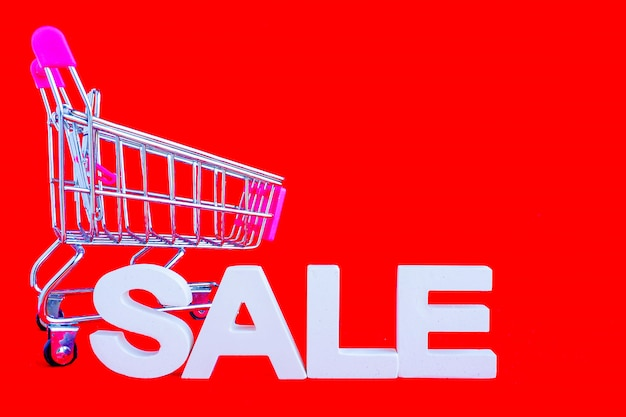 The word sale in white volume letters and a metal shopping trolley next to a red background.