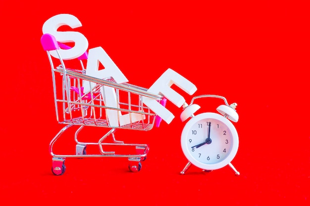 The word sale in white volume letters in a metal shopping trolley and a white alarm clock next to it on a red background.