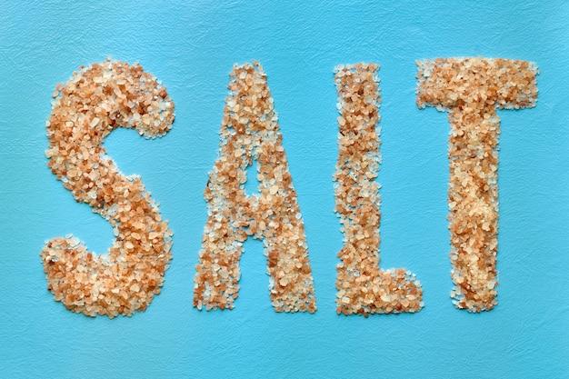 Word salt is made of coarse himalayan pink salt on blue