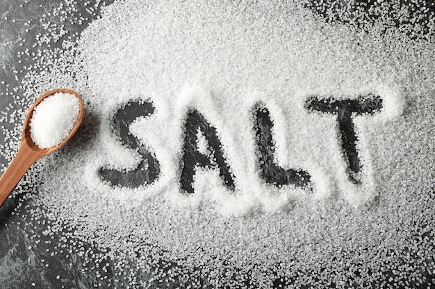 Слово соль из морской соли и ложки на черном дымчатом фоне