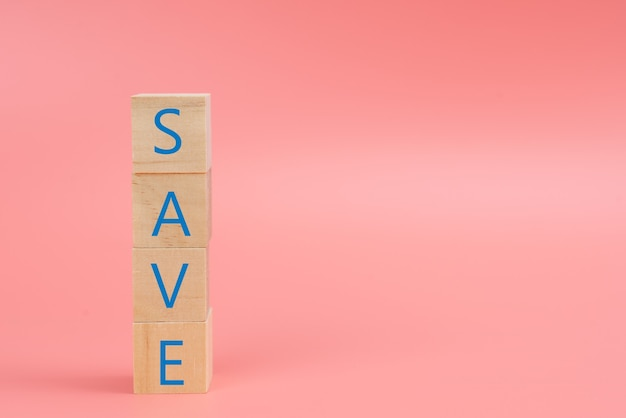 The word save on the wood block on pink background
