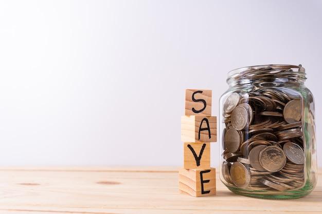 Сохранение слова, написанное на деревянных блоках рядом со стеклянной банкой с монетами на деревянном столе и белой стене