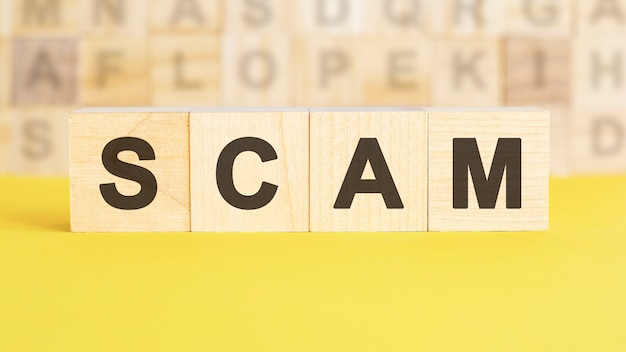 The word scam is written on wooden cubes on a bright yellow surface. in the background are rows of cubes with different letters. business and finance concept