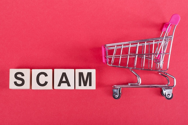 The word scam on wooden cubes on red desk with hand trolley