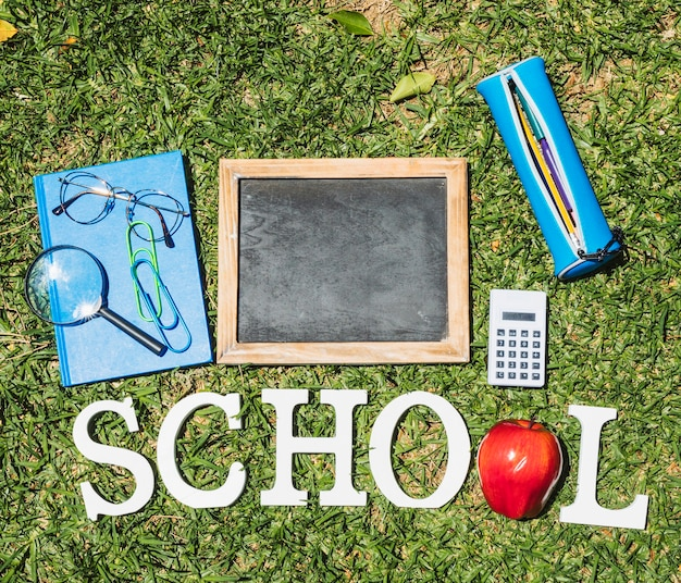 Word school next to stationery on grass