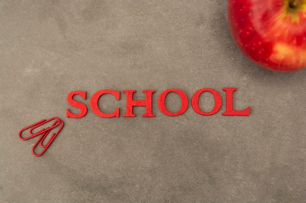 Word school with office supplies and red apple over black board. education concept.