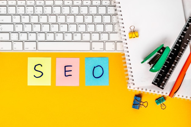 The word seo is written on colored stickers on the table with office supplies and keyboard
