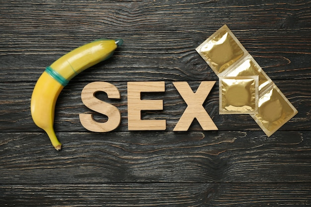 Word sex, banana and condoms on wooden surface