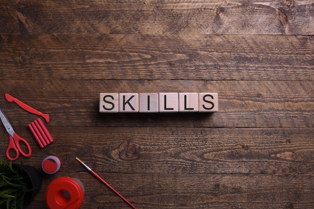 Word skills in wooden cubes, blocks on the subject of education, development and training on a wooden table. top view. place for text.