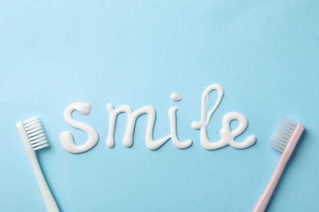 파란 표면에 치약으로 만든 단어 미소