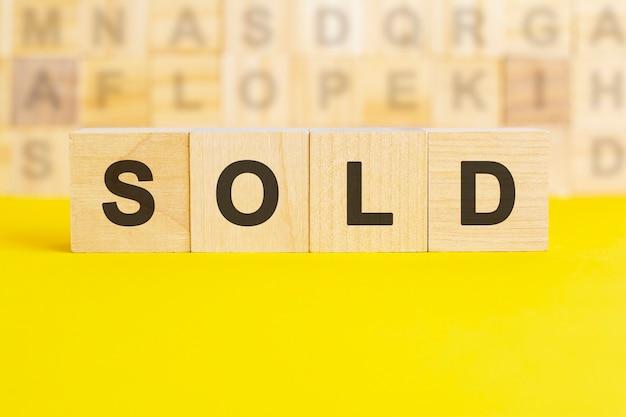 Слово продано написано на деревянных кубиках на ярко-желтой поверхности, концепция