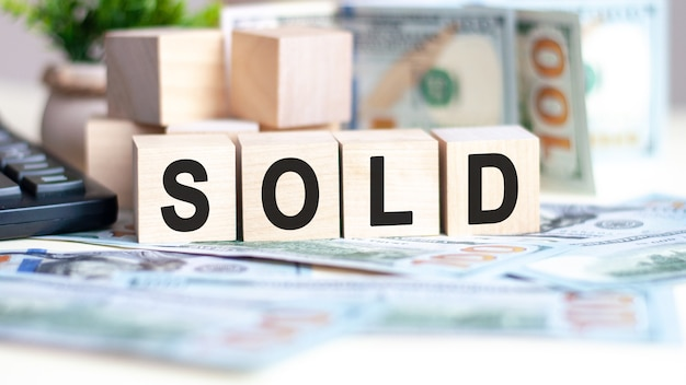 The word sold on wood cubes on banknotes and calculator