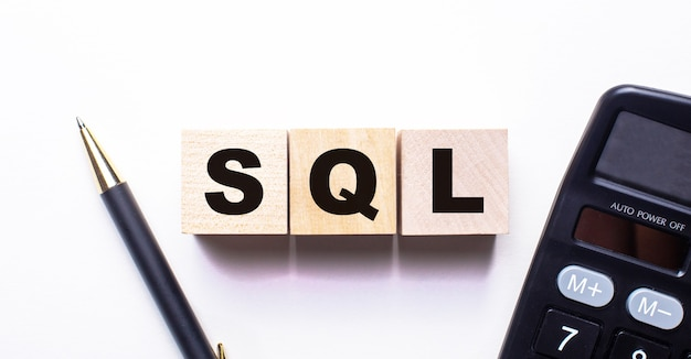 The word sql is written on wooden cubes between a pen and a calculator on a light wall.