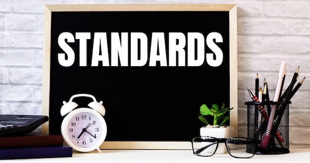 The word standards is written on the chalkboard next to the white alarm clock, glasses, potted plant, and pencils in a stand.