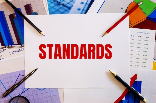 The word standards is written on a white wall near colored graphs, pens and pencils. business concept