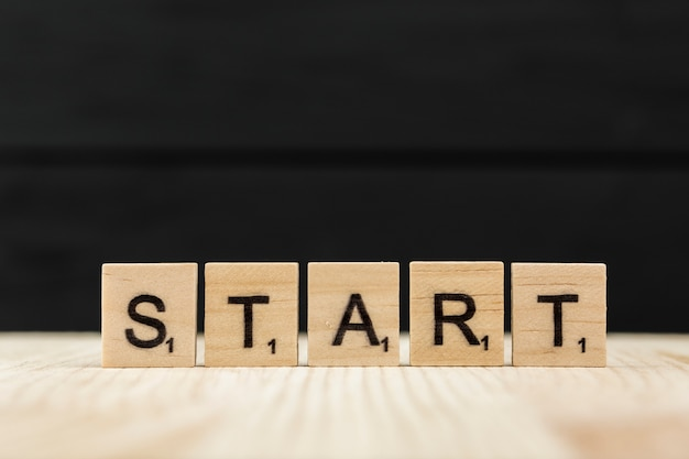 The word start spelt with wooden letters