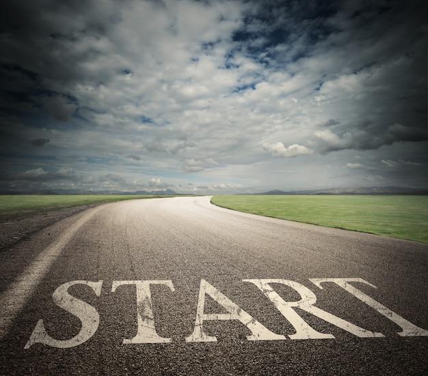 Слово начало написано на асфальтовой дороге с полевым ландшафтом