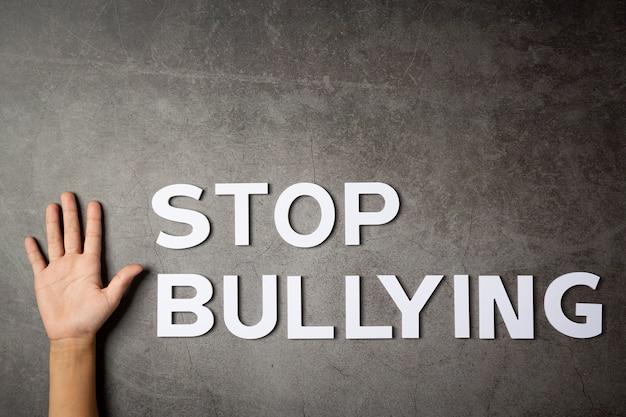 Слово «прекратите издевательства» с детской рукой на темной стене