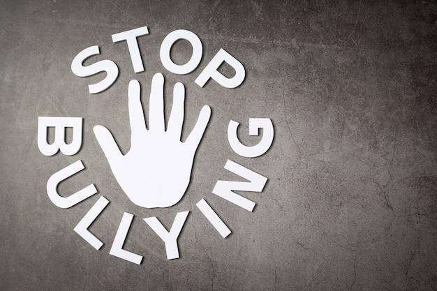Слово «прекратить издевательства» со знаком рукой на темной стене