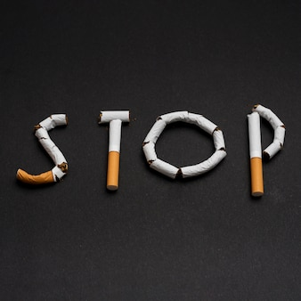 Word stop made from cigarettes above black background