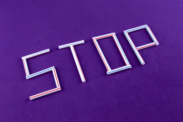 The word stop made of plastic tubes on purple