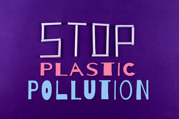 The word stop plastic pollution made of plastic tubes on purple