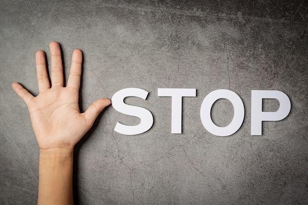 暗い壁に子供の手で「停止」という言葉