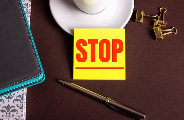 The word stop written on yellow paper on a brown background near a coffee cup and diaries