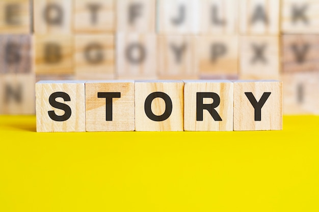The word story is written on wooden cubes on a bright yellow surface. in the background are rows of cubes with different letters. business and finance concept