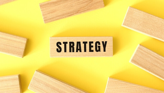 The word strategy is written on a wooden blocks on a yellow background.